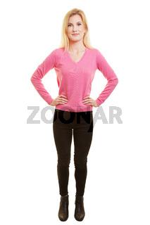 Junge blonde Frau frontal mit Händen in der Hüfte