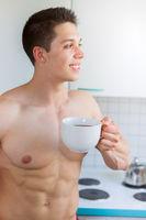 Bodybuilder junger Mann nachdenken Zukunft trinkt trinken Kaffee in der Küche Hochformat