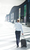 Business man walking with wheeled bag