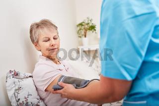 Blutdruck einer Seniorin wird kontrolliert