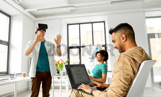 developers with virtual reality headset at office