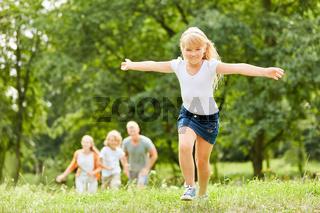 Blondes Mädchen läuft und tobt im Park