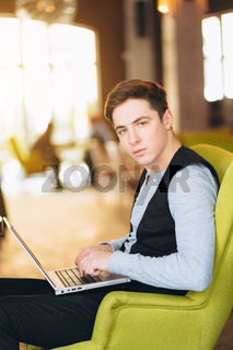Young man with pc computer sits in a comfortable chair