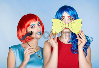 Females in red and blue wigs on blue background. Girls with yellow bow-tie and false moustashes