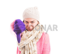 Woman wearing winter clothes showing thumb down