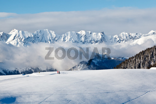 Panoramic View on Mountains and Two People Trekking in French Alps in Winter