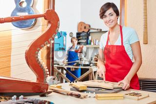 Frau als Gitarrenbauer in der Werkstatt