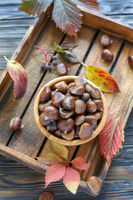 Bowl with ripe chestnuts on a wooden box.