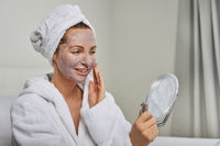 Attractive woman applying a face mask