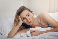 Woman propped up in bed staring at the camera