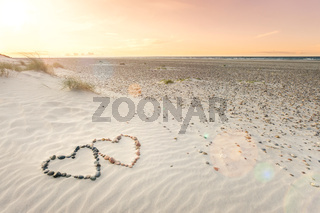Pebbles arranged in shape of two hearts on sand beach ripples with beautiful sunset.