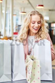 Junge Frau freut sich über ihre Einkäufe