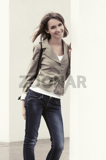 Happy young fashion woman with handbag standing at the wall