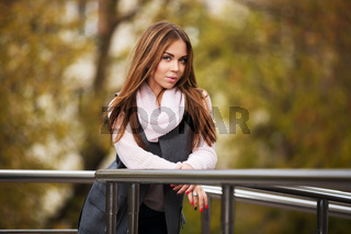 Young fashion woman in grey coat on city street
