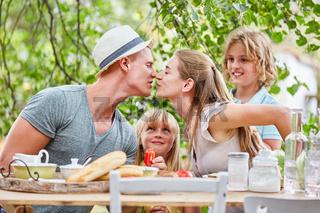Eltern küssen sich am Frühstückstisch