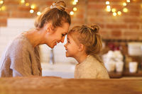 Beautiful woman and her daughter having fun indoors