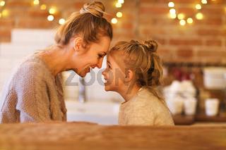 Beautiful woman and her daughter having fun indoors