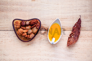 Selection food sources of omega 3 and unsaturated fats. Super food high vitamin e and dietary fiber for healthy food. Almond ,pecan,olive oil ,hazelnuts and walnuts on wooden background flat lay.