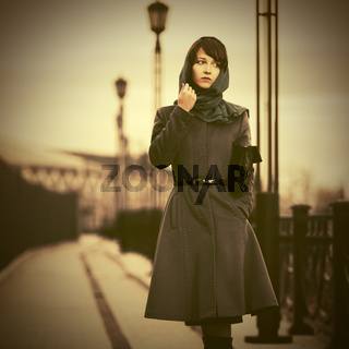 Sad young fashion woman in classic coat walking outdoor