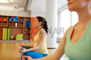 happy pregnant women meditating at gym yoga