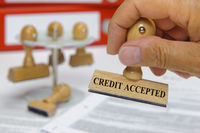 credit accepted printed on rubber stamp in hand