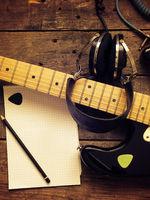 Vintage guitar with old studio headphones on wood
