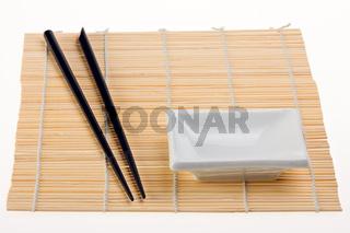 pair of chopsticks on a bamboo mat