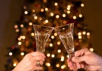 Champagne in two crystal flutes against christmas tree lights