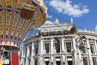 The historic Imperial Court Theatre at the famous Viennese Ringstrasse with some people enjoy a ride