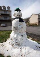 Melting snowman in housing development in spring