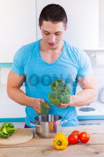Junger Mann kochen Essen Gemüse Mittagessen Hochformat in der Küche gesunde Ernährung