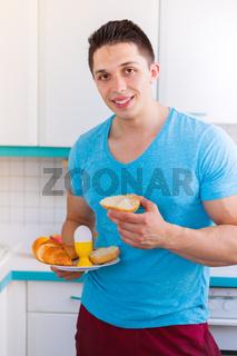 Frühstück essen junger Mann in der Küche Hochformat lachen morgens Morgen