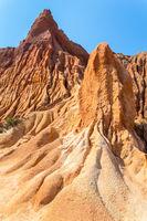 Steep weathered slopes of orange mountains