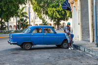 Havana, Cuba - December 12, 2016: Street scene in Old Havana. A cuban man standing next to his American classic car and smoking cigar