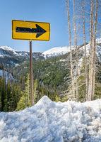 arrow road sign in mountain winter scenery