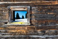 Vintage window of old wooden cabin mirrors winter mountain landscape. Wooden rustic background.
