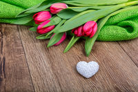 Red tulips and heart on a wooden table