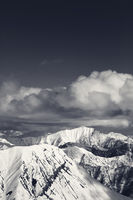 Winter snowy sunlit mountains and sky with clouds