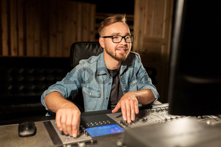man at mixing console in music recording studio