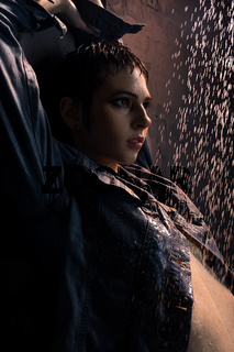 Brunette in wet jeans shirt in shower in the dark