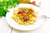 Farfalle with turkey and vegetables in sauce on table