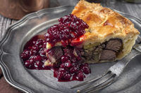 Venison Pie with Cranberry Relish as close-up on a pewter plate