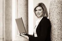 Young fashion business woman with laptop at office building