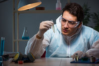Young male lab chemist late at night in overtime time