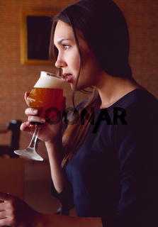 Young brunette drinking a beer in a restaurant
