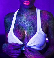 Sexy woman with UV fluorescent face and body makeup