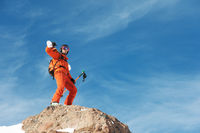 Portrait of a Skier in an orange overall with a backpack on his back and skis on his shoulders in a helmet stands on a rock against the blue sky.