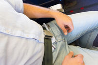 Male passenger with seat belt fastened while sitting on airplane for safe flight.