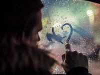 Man in love drawing heart on window