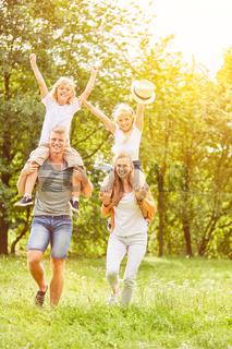Eltern tragen Kinder huckepack im Sommer